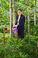 Portrait of an Asian businesswoman in a lush green forest watering ferns and grass with a watering can.