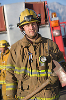 Portrait of firefighter holding axe