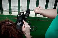 Palazzo San Gervasio (PZ) 14.06.2011 - Centro di Identificazione ed Espulsione. Una delegazione di parlamentari composta dai deputati Jean Leonard Touadi (Pd), Rosa Villecco Calipari (Pd) e Giuseppe Giulietti (Gruppo misto) - che oggi e' entrata nel Centro di identificazione ed espulsione (Cie) di Palazzo San Gervasio - ne ha chiesto ''l'immediata chiusura, per via delle inaccettabili condizioni di detenzione in cui versano 57 giovani tunisini''. Nella Foto: Una giornalista tenta di riprendere l'interno del Cie da un buco nella recinzione..Foto Giovanni Marino