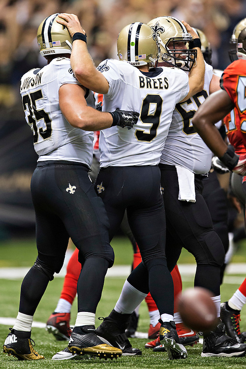 NEW ORLEANS, LA - SEPTEMBER 20:  Drew Brees #9 celebrates with Max Unger #60 and Austin Johnson #35 of the New Orleans Saints after a big play against the Tampa Bay Buccaneers at Mercedes-Benz Superdome on September 20, 2015 in New Orleans Louisiana. The Buccaneers defeated the Saints 26-19.  (Photo by Wesley Hitt/Getty Images) *** Local Caption *** Drew Brees; Austin Johnson; Max Unger