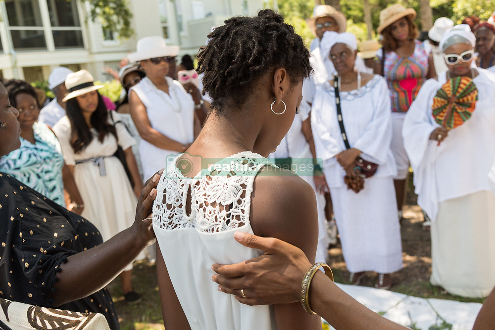 June 10, 2017 - Sullivan'S Island, South Carolina, United States of America - Descendants of enslaved Africans brought to Charleston in the Middle Passage hold a prayer service during a remembrance ceremony at Fort Moutrie National Monument June 10, 2017 in Sullivan's Island, South Carolina. The Middle Passage refers to the triangular trade in which millions of Africans were shipped to the New World as part of the Atlantic slave trade. An estimated 15% of the Africans died at sea and considerably more in the process of capturing and transporting. The total number of African deaths directly attributable to the Middle Passage voyage is estimated at up to two million African deaths. (Credit Image: © Richard Ellis via ZUMA Wire)