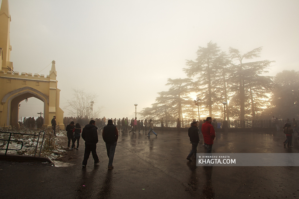 People walk past the christ church of shimla with their friends in a yellow foggy evening after the first snowfall of the season