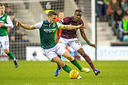 Paul Hanlon (#4) of Hibernian FC shields the ball from Arnaud Djoum (#10) of Heart of Midlothian during the Ladbrokes Scottish Premiership match between Hibernian FC and Heart of Midlothian FC at Easter Road Stadium, Edinburgh, Scotland on 29 December 2018.