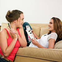pictures in a living room of two young girls sitting on a couch laughing calling by phone and watching magazine