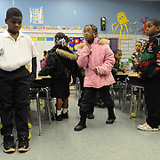 JaJuan, far left, tucks his arms inside his shirt. The heat has gone out at his elementary school and JaJuan does not own a winter jacket. The school allowed him to borrow one to wear throughout the school day.