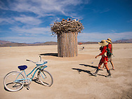 Two people dressed in red walk past a 'nest' art installation, with decorated blue burning bike, Burning Man Festival.