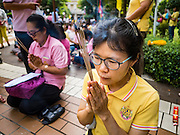 13 OCTOBER 2016 - BANGKOK, THAILAND: Women pray for Bhumibol Adulyadej, the King of Thailand, at Siriraj Hospital Thursday morning before the King's death was announced. Thousands of people came to the hospital to pray for the beloved monarch. Bhumibol Adulyadej, the King of Thailand, died at Siriraj Hospital in Bangkok Wednesday, October 13, 2016. Bhumibol Adulyadej, 5 December 1927 – 13 October 2016, was the ninth monarch of Thailand from the Chakri Dynasty and is known as Rama IX. He became King on June 9, 1946 and served as King of Thailand for 70 years, 126 days. He was, at the time of his death, the world's longest-serving head of state and the longest-reigning monarch in Thai history.       PHOTO BY JACK KURTZ