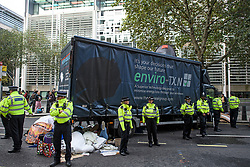 © Licensed to London News Pictures. 08/10/2019. London, UK. Extinction Rebellion activists glued underneath a lorry outside the Department for Environment, Food and Rural Affairs in Westminster. Activists have converged on Westminster for a second day, blockading roads in the area and calling on government departments to 'Tell the Truth' about what they are doing to tackle the Emergency. Photo credit: Ben Cawthra/LNP