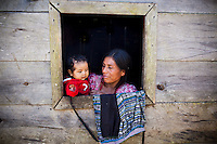A woman with her grandson in the window of her wooden home, in a remote village outside of Uspantan, Guatemala, on March 28, 2012. Many indigenous Guatemalans were accused by the government of harboring leftist guerrillas. Villagers here fled to the mountains where they lived for 12 years when the military came and burned their homes, raped the women and forced men into civic patrols.