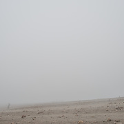 A hiker is almost completely obscured by the dense fog high on Mt Kilimanjaro. At these altitudes the weather can change drastically very quickly.
