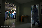 Cipla Director of Corporate Affairs Rynard Van Der Westhuizen watches as Plastic Surgeon Team Leader Conrad Pienaar and OR Nurse Bridget Lavery begin surgery on patient 020, Ephraim Moyo, 29 Years old, Male, UCL, before.<br /> Operation Smile South Africa&rsquo;s 2015 mission to Mbombela. South Africa.<br /> <br /> (Operation Smile Photo - Zute Lightfoot)