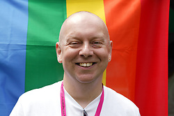Portrait of a man in front of the rainbow flag at the Nottingham Pride Gay Lesbian festival; held at the Arboretum,