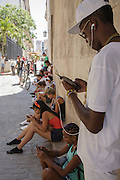 Young people using a public outdoor wifi hotspot in calle Obispo, Havana, Cuba
