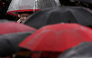 Britain's Queen Elizabeth is almost hidden by umbrellas during a downpour outside the provincial legislature in Regina, Sask during a western Canadian tour. (2005)