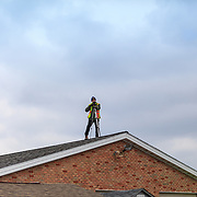 Bart, PA - March 2, 2013: A photographer on a rooftop taking photos of people at an Amish mud sale in Lancaster County.
