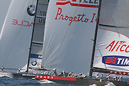 Italy's Luna Rossa foredeck crew stows genoa jib after hoisting spinnaker and rounding mark beside USA's BMW Oracle Racing team during America's Cup fleet race; Valencia, Spain.