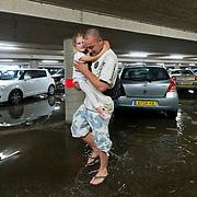 Foto: David Rozing Nederland Barendrecht 27 juli 2013 20130727 Garage van van Albert Heijn is door de hoosbuien ondergelopen met water. Bezoekers halen natte voeten om de winkel te betreden en verlaten met de boodschappen. Foto: David Rozing