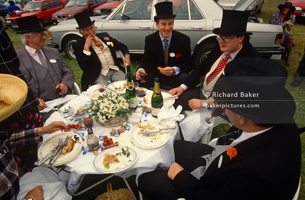In a grassy car park on Ladies Day at Royal Ascot racing week, a group of men (and one unseen lady) talk and relax, one smoking a cigar surrounded by the remains of a generous picnic lunch with a bouquet of flowers on their table. Trays of food and two bottles of Champagne have been consumed during a break from betting and socialising. They are dressed in formal morning dress of top hat, waistcoat, tails with two of the men wearing red roses in their lapel button holes, all traditional and obligatory dress code in the Royal Enclosures which can be seen by visitors in the public car parks near the famous Berkshire race course. In the background we see a silver Rolls-Royce car and a lady sitting in its boot (trunk) also eating picnic food. The day is overcast, but despite this, they are in a joking and excitable mood. Royal Ascot is held every June and is one of the main dates on the sporting calendar and social season.