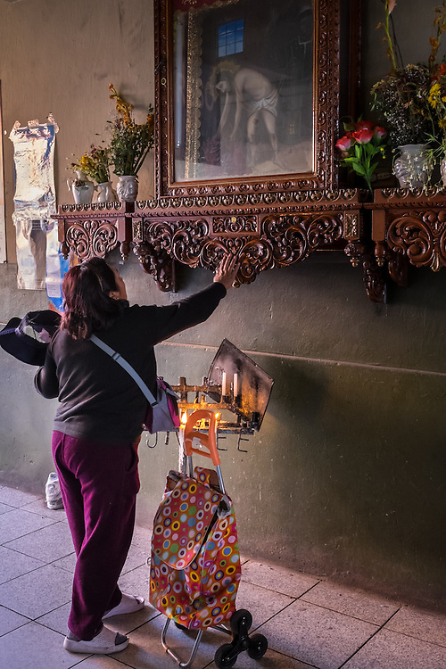 AREQUIPA, PERU - CIRCA APRIL 2014: Peruvian woman worshiping at one the entrances of the San Camilo market in. Arequipa is the Second city of Perú by population with 861,145 inhabitants and is the second most industrialized and commercial city of Peru.