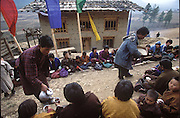 Friends and neighbors come to join in a housewarming ceremony for the new rammed earth house behind them, in Gangte, Bhutan. (Supporting image from the project Hungry Planet: What the World Eats.)