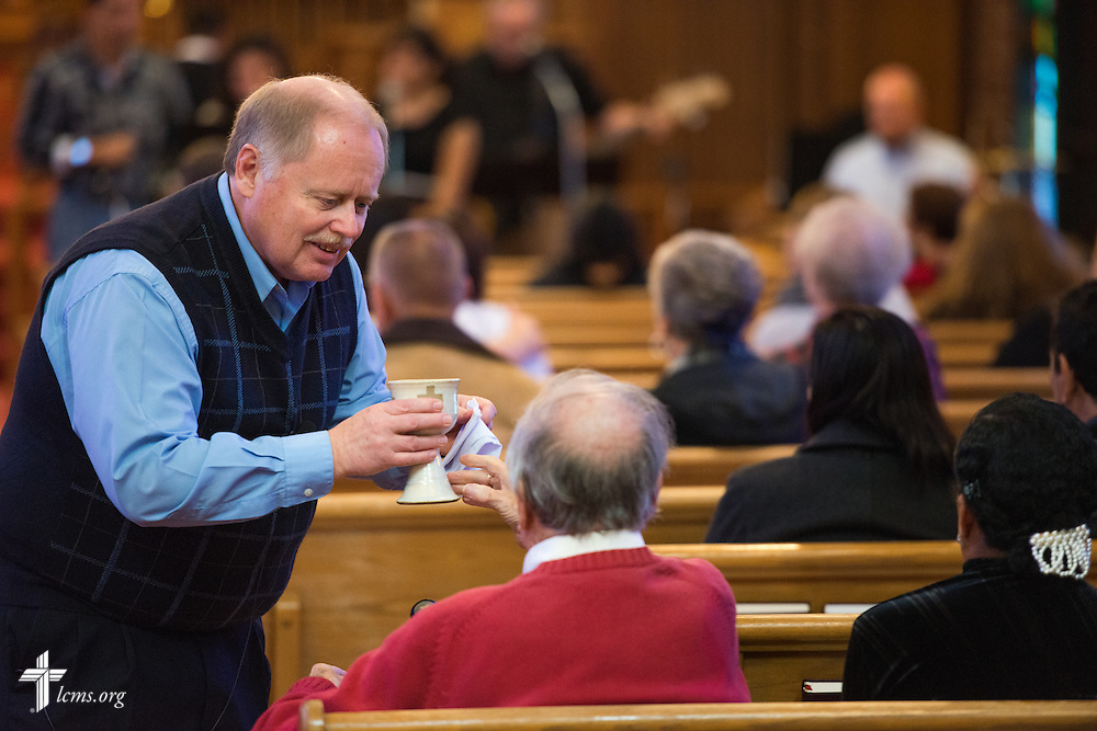 The Rev. Mark E. Krause, senior pastor, distributes the sacrament during communion at a monthly bilingual worship on Sunday, Nov. 22, 2015, at Salem Lutheran Church in Springdale, Ark. LCMS Communications/Erik M. Lunsford