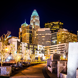 Charlotte skyline with Romare Bearden Park sidewalk at night. Charlotte, North Carolina is a major city in the Eastern United States of America. Includes Bank of America Corporate Center, Bank of America Plaza, and 121 West Trade buildings.