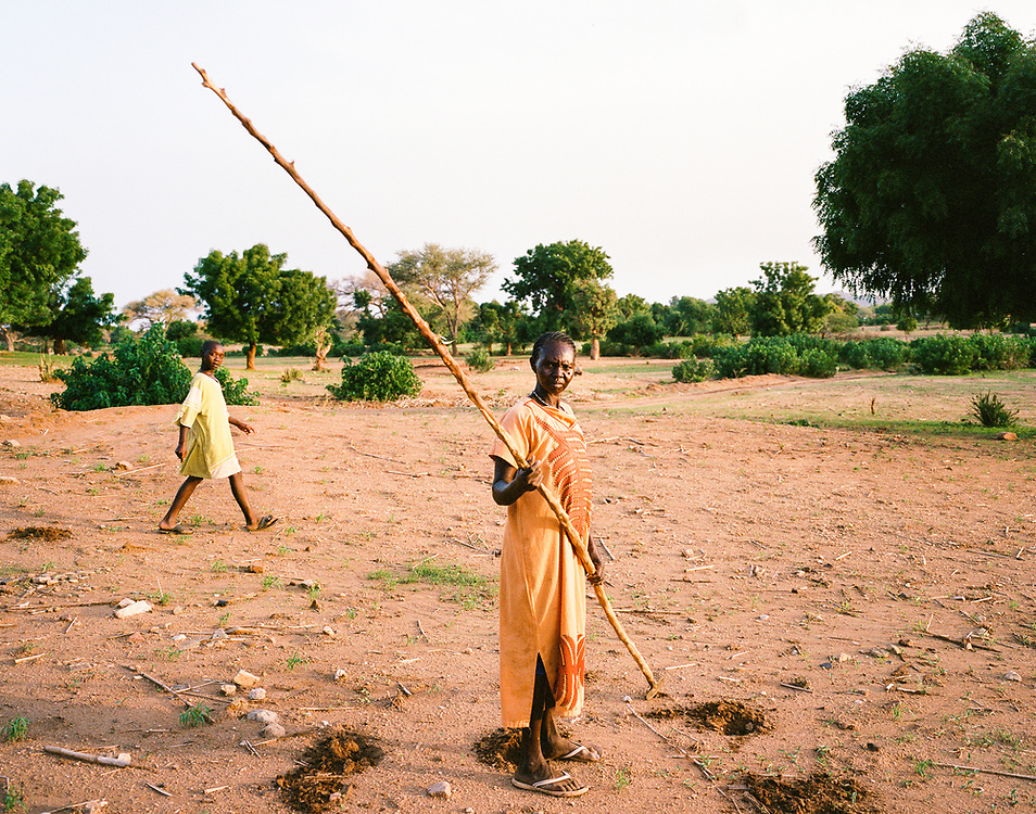 "NUBA MOUNTAINS, SUDAN – JUNE 9, 2018: A woman prepares to plant crops on the outskirts of Kouda, the cultural center of Hieban County.<br /> <br /> In 2011, the government of Sudan expelled all humanitarian groups from the country's Nuba Mountains. Since then, the Antonov aircraft has terrorized the Nuba people, dropping more than 4,080 bombs on hospitals, schools, marketplaces and churches. Today, vestiges of the Antonov riddle the landscapes of daily life, where more than 1 million Nuba live in famine conditions – quietly enduring the humanitarian blockade intended to drive them out of the region. The skies are mostly clear. Yet the collective memory of the bombings remains an open wound, and the Antonov itself a persistent threat. So frequent were the attacks that the Nuba nicknamed the high flying aircraft and its dismal hum: ""Gafal-nia ja,"" they would declare, running to the hillsides. ""The loss of appetite has come."""