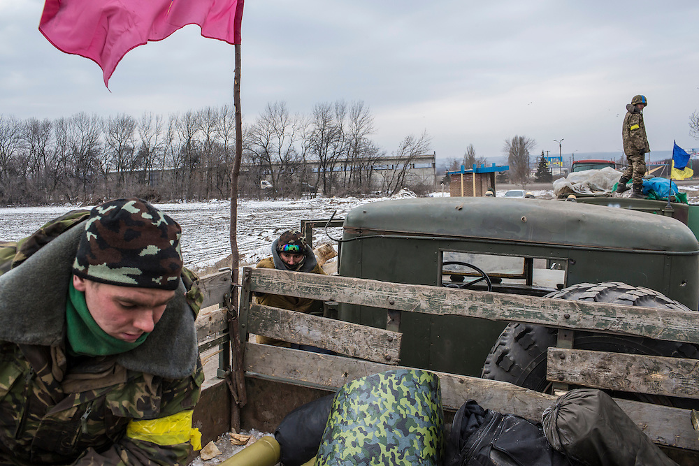 ARTEMIVSK, UKRAINE - FEBRUARY 19: Ukrainian soldiers from a unit based in Zaporizhia raise the Zaporizhia flag on their truck after withdrawing from Debaltseve the previous day on February 19, 2015 in Artemivsk, Ukraine. Ukrainian forces started withdrawing from the strategic and hard-fought town of Debaltseve yesterday being effectively surrounded by pro-Russian rebels. (Photo by Brendan Hoffman/Getty Images) *** Local Caption ***