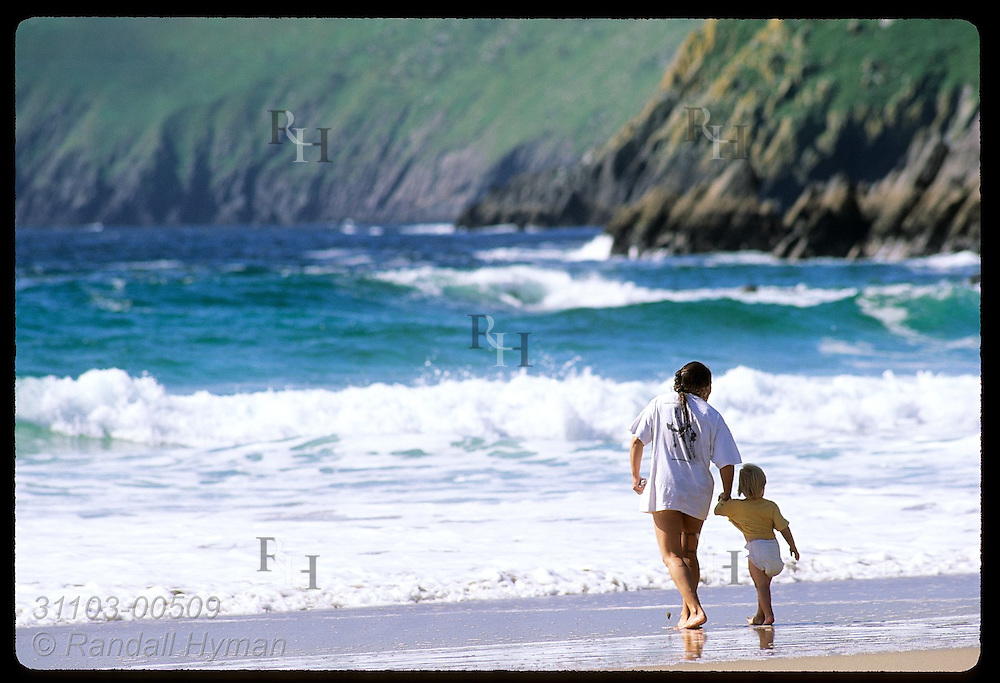 Mom & diaper girl wet toes in the chilly North Atlantic surf of Coumeenole Beach with Dunmore Head in distance; Dingle, Ireland.