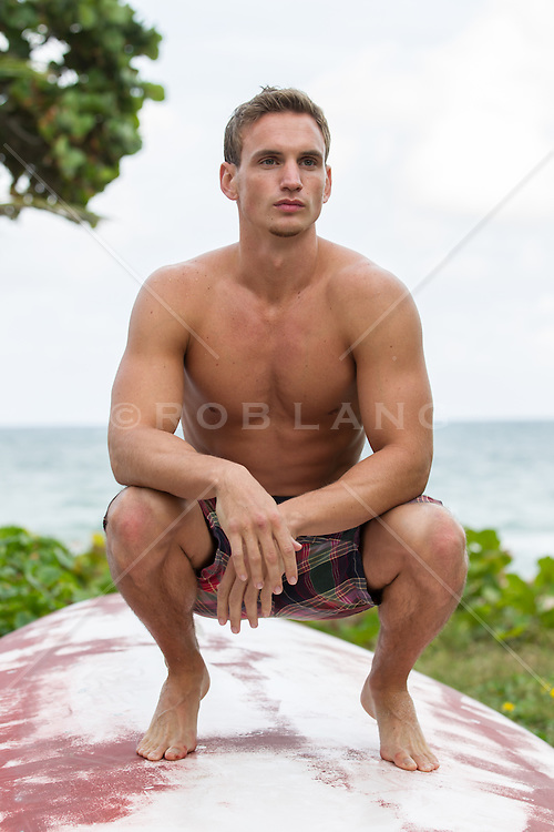 hot man at the beach squatting down on a boat