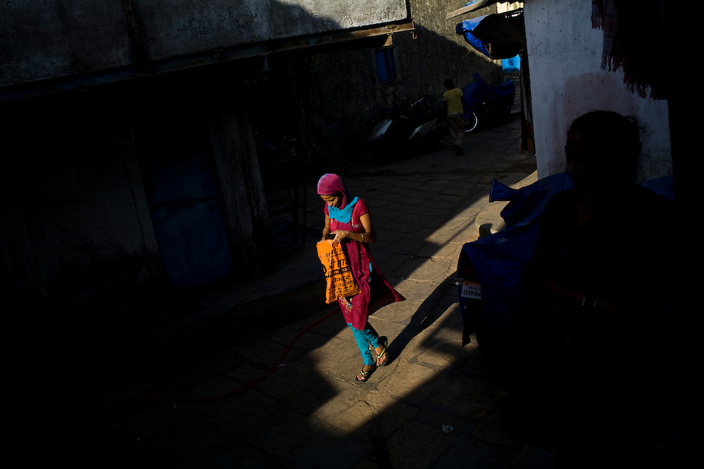 A youn girl walks through the Rafik Nagar slum, one of the areas in which Lok Seva Sangam, a local NGO, has set up free TB health clinics.  People in the slums are often too poor to pay for proper health care, let alone the transportation to get them to the hospitals or clinics.