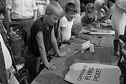 Children watch as community arts workers silkscreening  clothing with support slogans. Cortonwood Gala Day. Brampton Brierlow 25/08/1984.
