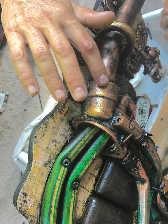 Julio Cepeda'a hand smooths gold over 3-D found object art, West Reading, Berks Co. PA