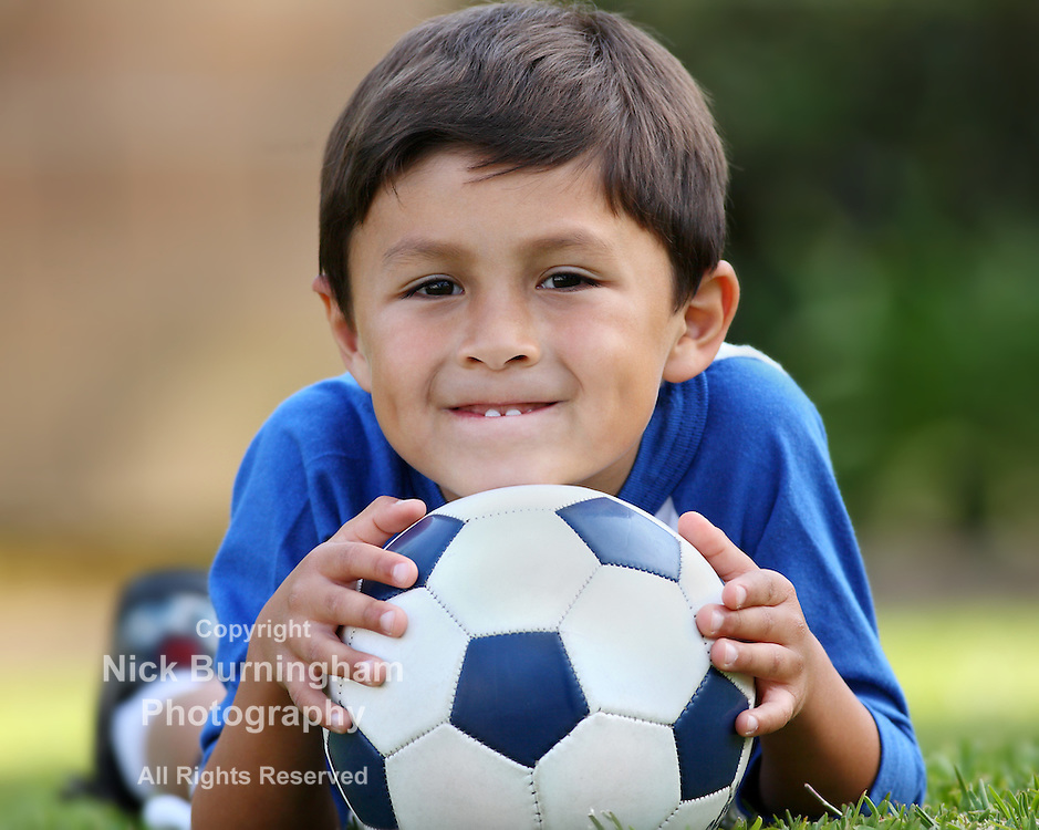 Young brown haired hispanic boy in blue shirt lying down on grass with soccer ball in hands