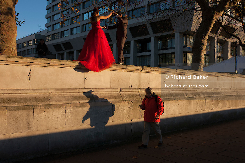 A young couple pose for wedding photos on the Southbank, on 29th November 2016, in London England.