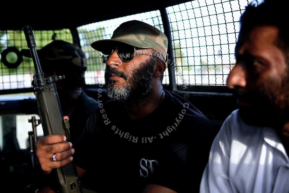 An armed member of the AVCC, (Anti-Violence Crime Cell) a special police unit mostly involved in anti-terrorism operations and kidnap cases in the city of Karachi, is sitting in a police van on the way to a night raid on the outskirts of Karachi, Pakistan's main economic hub.