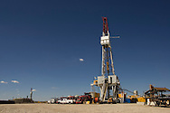 """PINEDALE, WY - The Caza drill rig 86 on the Pinedale Anticline near Pinedale, Wy., (pop. 1400) on August 18, 2005. """"We're doing our best to keep the Californians from freezing to death in the dark,"""" jokes company man Chris Holten, who has been an engineer in the petroleum industry for years. Questar, one of the main natural gas lease holders in Sublette County, which encompasses the Jonah Field, was recently granted approval for year-round drilling operations in the Pinedale Anticline, an environmentally sensitive winter forage ground for big game, part of the longest big game migration route in the lower 48, as well as hosting the largest remaining population of sage grouse. Some of the reasons for approval were Questar's proposal of fewer drill pads, more directional drilling, and a pipeline to transport condensate and water out of the environmentally sensitive areas. Critics say these changes should have been standard in the initial drilling permit which, were it to be followed, would have amounted to a greater overall environmental impact than the newly approved plan. Year-round drilling will allow the company to develop its wells in about half the time (10 years vs. 18 years) and to stabilize a seasonal influx of workers, allowing contracted employees to take up residence in the area instead of spending the summers in company man-camps or the area hotels. In the nearby Jonah Field where operators are seeking an 'in-fill' project with the number of cheaper straight-down wells increasing from 533 to 3100, Encana, one of the chief operators, is expected to drill two thirds of the wells to yield upwards of 10.5 trillion cubic feet of natural gas which has a current market value of $55 to $60 billion dollars. Encana could make $2 billion in profit per TCF depending price trends and production costs. Amongst Pinedale Anticline engineers there is already talk of in-fill projects and deep wells reaching down to 20,000 feet. Current wells are in the 11,000-15,000 foot d"""