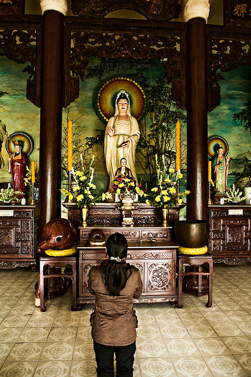 Young Vietnamese woman kneeling in pryaer before a statue of the Goddess of Mercy (Quan Yin)  in a Central Vietnam village Buddhist pagoda.  She is seen from the back.  The statue of the goddess on the altar is dressed in white, with a halo, echoing in appearance the Virgin Mary in some Roman Catholic practice..