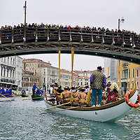 VENICE, ITALY - FEBRUARY 20:  Boats from from several rawing association reach a crowded Accademia fridge and sail along the Grand Canal during the Venetian Feast on February 20, 2011 in Venice, Italy. During the Venetian Feast a traditional water parade sails from San Marco along the Canal Grande to the  district of Cannaregio where there the crowd waits for the Svolo della Pantegana  (flight of the mouse).