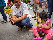"22 JULY 2013 - PHRA PHUTTHABAT, THAILAND:  A man and his daughter wait for the monks to walk through the crowd at the Tak Bat Dok Mai at Wat Phra Phutthabat in Saraburi province of Thailand, Monday, July 22. Wat Phra Phutthabat is famous for the way it marks the beginning of Vassa, the three-month annual retreat observed by Theravada monks and nuns. The temple is highly revered in Thailand because it houses a footstep of the Buddha. On the first day of Vassa (or Buddhist Lent) people come to the temple to ""make merit"" and present the monks there with dancing lady ginger flowers, which only bloom in the weeks leading up Vassa. They also present monks with candles and wash their feet. During Vassa, monks and nuns remain inside monasteries and temple grounds, devoting their time to intensive meditation and study. Laypeople support the monastic sangha by bringing food, candles and other offerings to temples. Laypeople also often observe Vassa by giving up something, such as smoking or eating meat. For this reason, westerners sometimes call Vassa the ""Buddhist Lent.""    PHOTO BY JACK KURTZ"