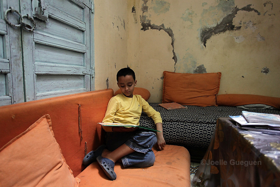 Simo, 9 years old reads in the living room of his home; Marrakech Medina - May 2013