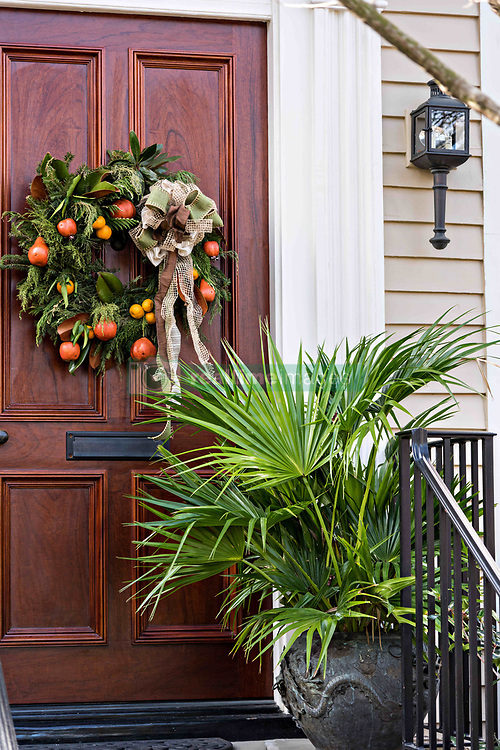 December 21, 2017 - Charleston, South Carolina, United States of America - A traditional low country Christmas wreath decorated with fruit hangs from a wooden door on a historic home along King Street in Charleston, SC. (Credit Image: © Richard Ellis via ZUMA Wire)