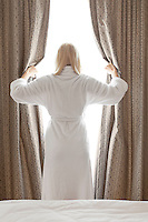 Rear view of young woman in bathrobe opening bedroom curtains at hotel room