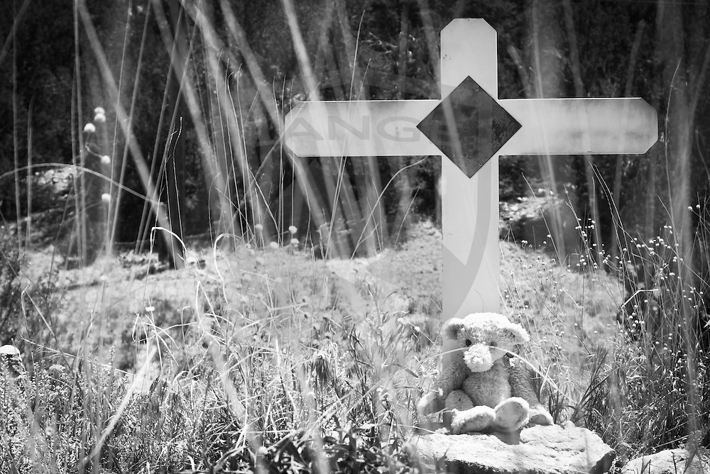 a roadside grave with cross and stuffed animal teddy bear in black and white is a grim reminder memoralizing a traffic fatality in the town of tijeras, new mexico
