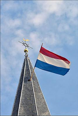 Nederland, Lunteren, 16-4-2015Uit een kerktoren, de toren van een kerk, hangt de nederlandse valg strak te wapperen tegen een blauwe lucht.FOTO: FLIP FRANSSEN/ HOLLANDSE HOOGTE