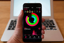 Using iPhone smartphone to display Apple health app displaying amount of physical activity undertaken each day