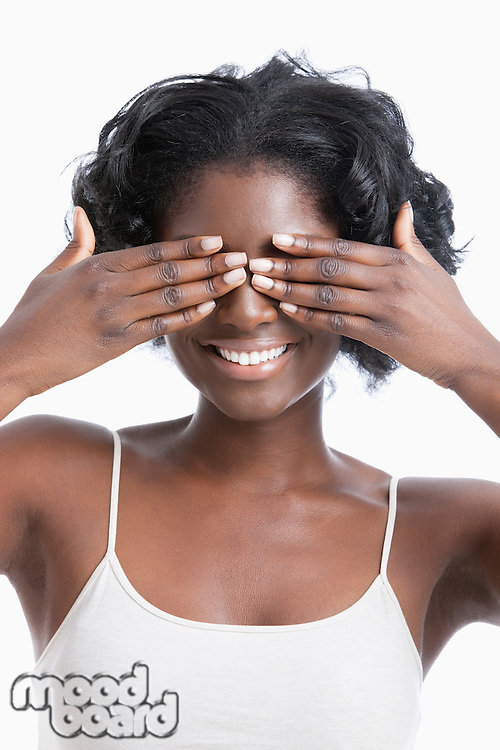 Playful young African American woman covering eyes against white background