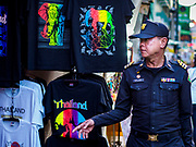 01 AUGUST 2018 - BANGKOK, THAILAND:     A Bangkok code enforcement supervisor walks past a market stall selling tee shirts on Khao San Road in Bangkok. Khao San Road is Bangkok's original backpacker district and is still a popular hub for travelers, with an active night market and many street food stalls. The Bangkok municipal government went through with it plans to reduce the impact of the street market on August 1 because city officials say the venders, who set up on sidewalks and public streets, pose a threat to public safety and could impede emergency vehicles. Venders are restricted to working from 6PM to midnight and fewer venders will be allowed to set up on the street. It's the latest in a series of night markets and street markets the city has closed.    PHOTO BY JACK KURTZ