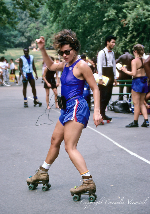 Young woman with a walkman and old-fashioned roller skates dancing at the roller disco in Central Park, New York City.