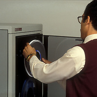 A man loads a reel of tape into a Hewlett-Packard mainframe computer storage unit in 1985.